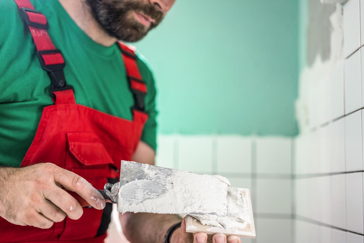 Tile mason spreading adhesive on ceramic tile