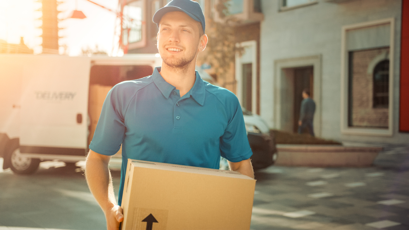 Portrait of Delivery Man Holds Cardboard Box Package Standing in Modern Stylish Business District with Delivery Van in Background. Smiling Courier On Way to Deliver Postal Parcel to Client. Sun Flare
