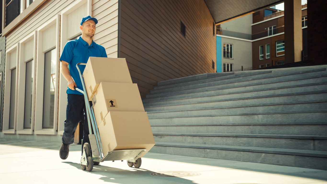 Happy Young Delivery Man Pushes Hand Truck Trolley Full of Cardboard Boxes and Packages For Delivery. Professional Courier Working Efficiently and Quickly. In the Background Stylish Modern Urban Area