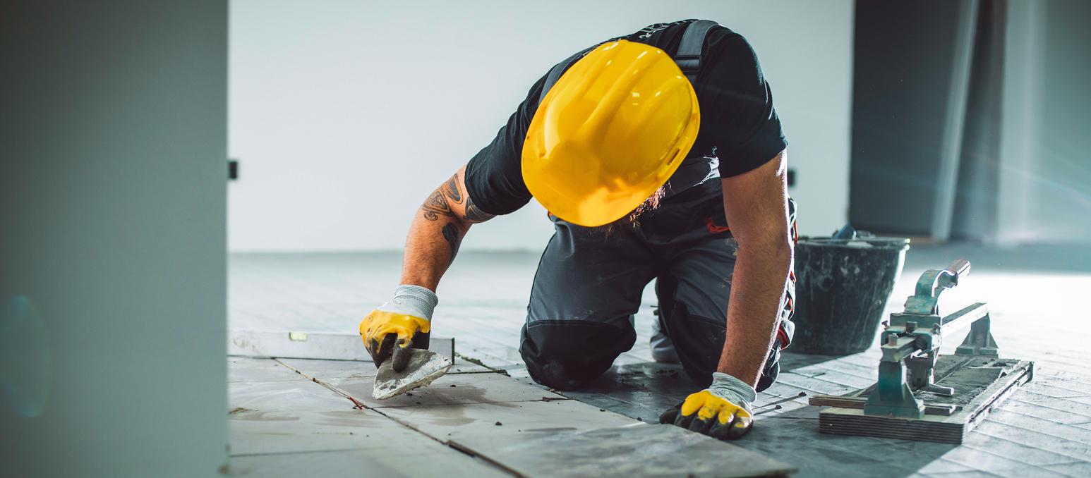 Master installer laying tile