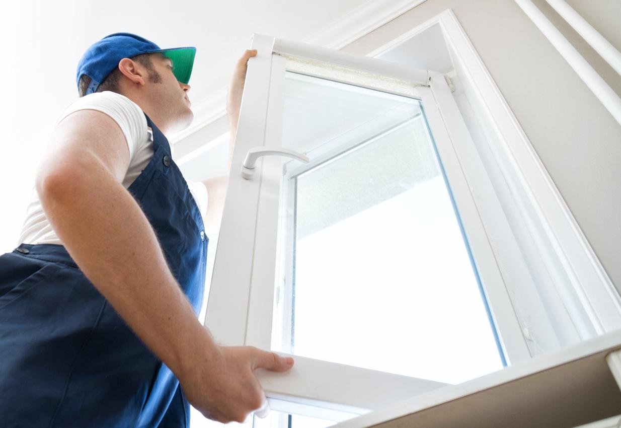Professional handyman installing window at home.
