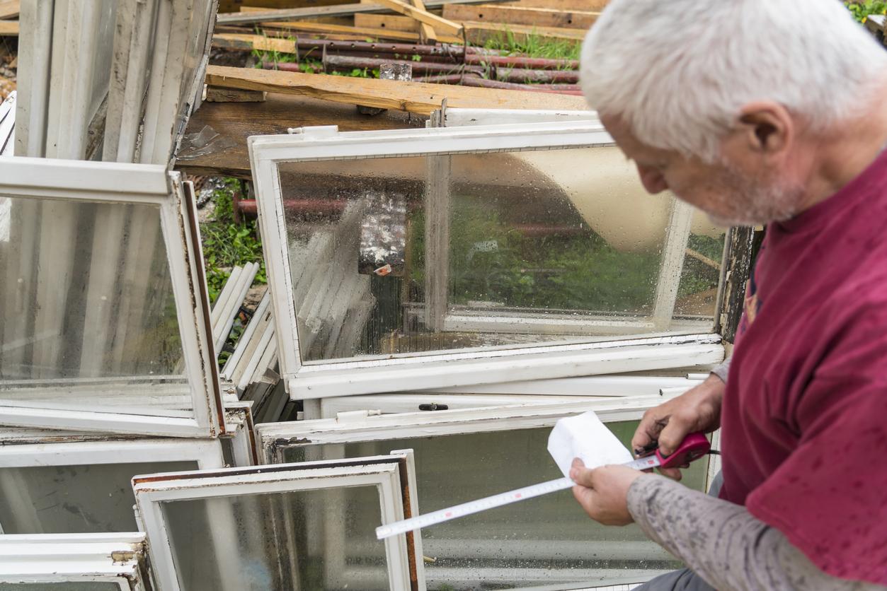 Man looking old window frames - construction debris